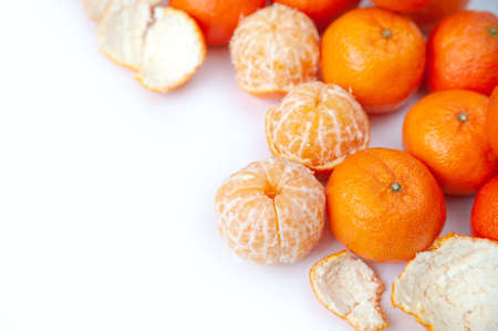 peeled tangerines on a white background. skins. slices