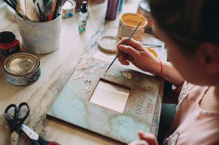 girl paints the frame with a brush. handwork. creation Zdjęcie Seryjne - 124145885