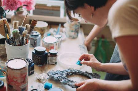 girl paints the frame with a brush. handwork. creation Zdjęcie Seryjne - 124145890