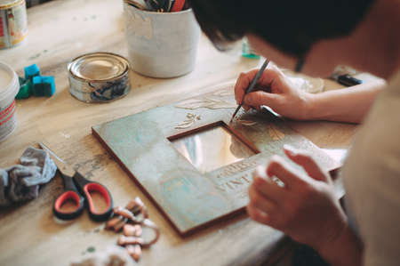 girl paints the frame with a brush. handwork. creation Stock Photo - 124145891