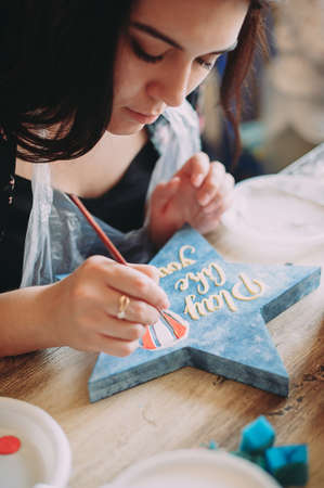 girl paints the frame with a brush. handwork. creation Stock Photo - 124145892