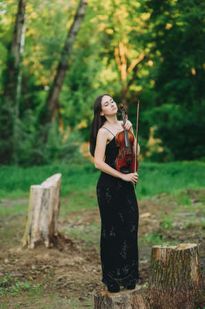 A young woman playing the violin in a magical forest. Standing on a stump
