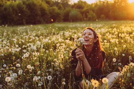 Beautiful Young Woman lying on the field in green grass and blowing dandelion. Outdoors. Enjoy Nature. Healthy Smiling. Allergy free concept. Freedom Zdjęcie Seryjne - 124145908