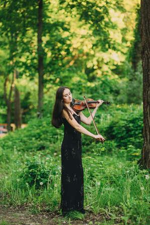 Beautiful girl in a black dress plays the violin in the woods Zdjęcie Seryjne - 124145910