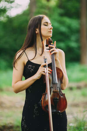 beautiful girl holding a violin in her hands. violinist in the forest Zdjęcie Seryjne - 124145912