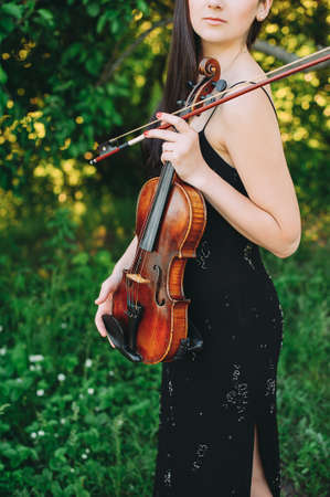 beautiful girl holding a violin in her hands. violinist in the forest 스톡 콘텐츠