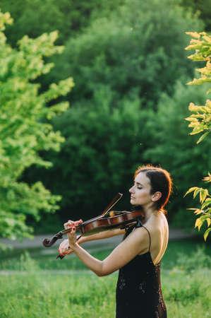 Beautiful girl in a black dress plays the violin in the woods Zdjęcie Seryjne - 124145914