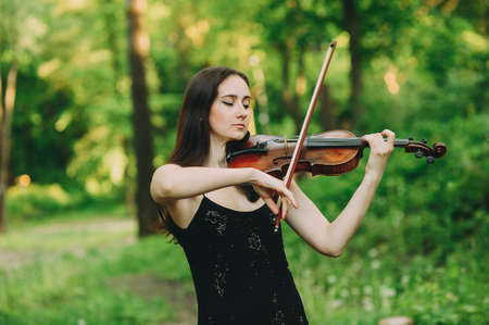 Beautiful girl in a black dress plays the violin in the woods Reklamní fotografie - 124145915