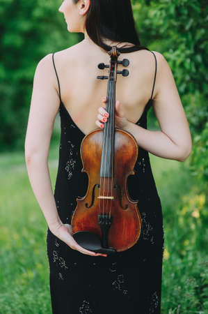 Violin in the hands of a beautiful woman in a black dress Zdjęcie Seryjne - 124145916