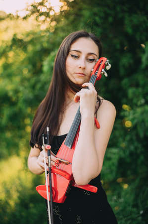 Beautiful girl with long hair holds a red electronic violin in her hand Zdjęcie Seryjne - 124145921