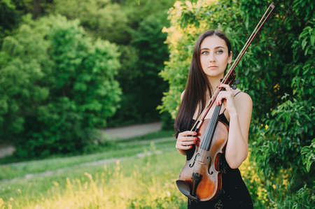 Beautiful girl with a violin on nature. long hair