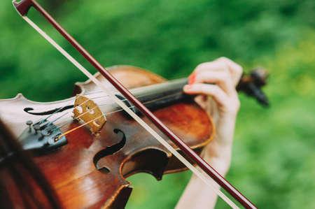 Belle fille en robe noire joue du violon dans les bois