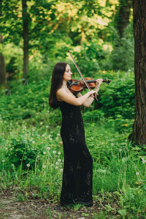 Beautiful girl in a black dress plays the violin in the woods