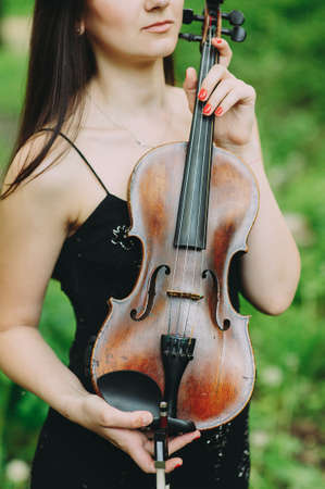 beautiful girl holding a violin in her hands. violinist in the forest Zdjęcie Seryjne
