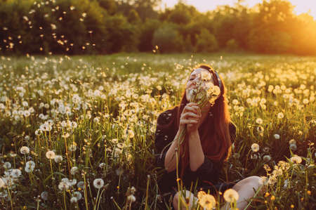 young woman with dandelions in hand in a field against the evening sun. sunset. joy. smile