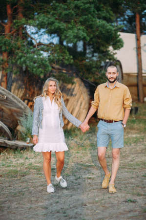 A happy young couple walking by nature, a pregnant girl, a bearded man. Love. The concept of pregnancy Zdjęcie Seryjne