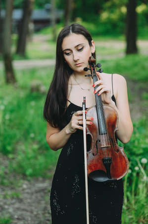 beautiful girl holding a violin in her hands. violinist in the forest Stok Fotoğraf