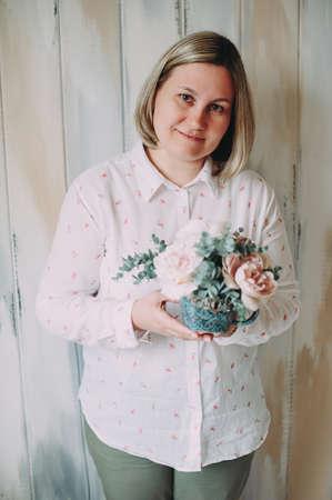 Flower arrangement in the hands of a woman florist in decor studio Stock Photo