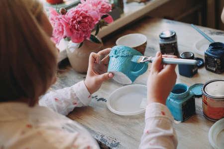 Vrouw aan het werk in haar pottenbakkerij. Keramische werkplaats. Verf op kleikop in het aardewerk. Schilderen in aardewerk