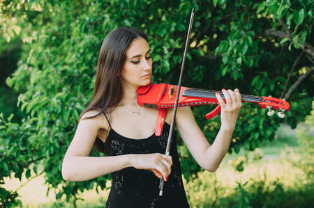 Beautiful girl with long hair holds a red electronic violin in her hand Stok Fotoğraf