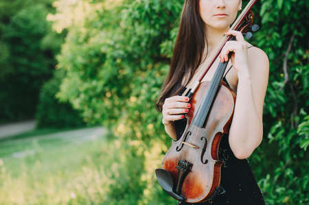 Beautiful girl with dark hair holds an old violin in her hands. Violinist