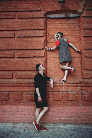 美しいヒップスターの女の子とハンサムな若い男は外の階段に座って、週末に白いスマートフォンで自分撮りを取っています。レクリエーション時間中にビデオを撮影幸せなロマンチックなカップル