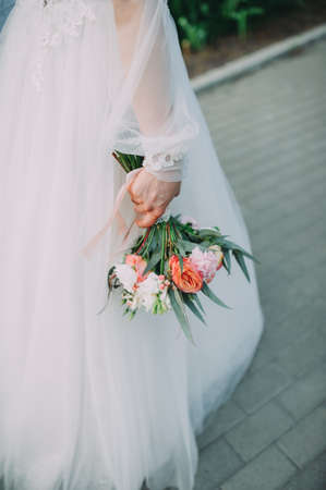 beautiful bouquet of different colors in the hands of the bride in a white dress Stock Photo