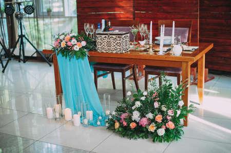 Wedding decor. Newlyweds table. Fresh flowers, candles