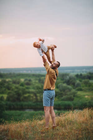 Happy father throws up baby in nature
