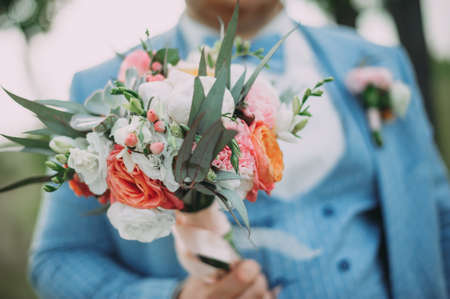 the groom holds in his hands a beautiful wedding bouquet of different flowers