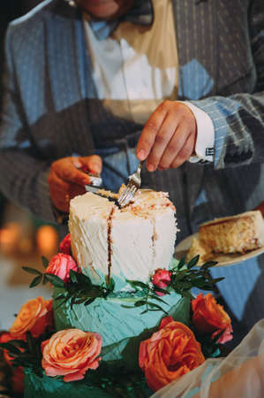 groom cuts a wedding cake. beautiful wedding cake in blue with red flowers