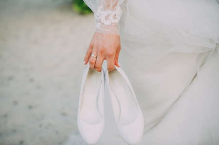 bride holding a shoe in her hand