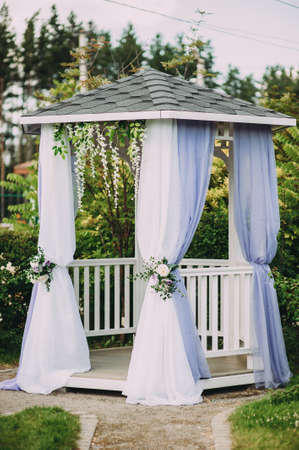 Beautiful white wedding arch made of fabric. decor