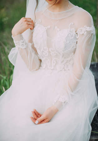 beautiful bride in a wedding dress sitting hands clasped