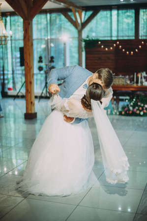the first dance of the newlyweds at a wedding in a restaurant. kiss