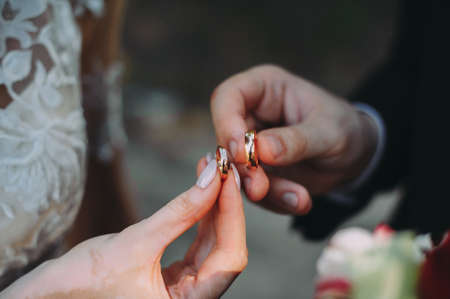 gold wedding rings in the hands of the newlyweds