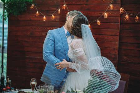 Newlyweds kiss at a wedding at the table