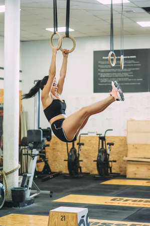 young girl doing exercises on sports rings