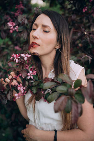 beautiful brunette in a white blouse posing on a background of flowers