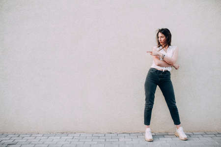 Modern stylish woman in big white sneakers posing against a wall. Fooling around
