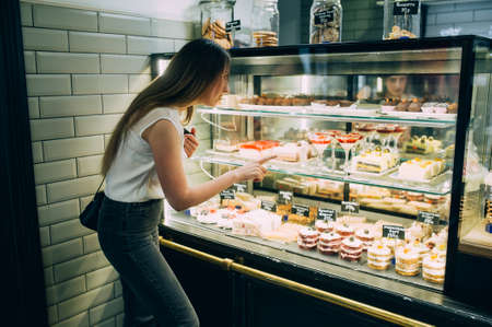 stylish girl with long hair near the window with sweets. chooses cake