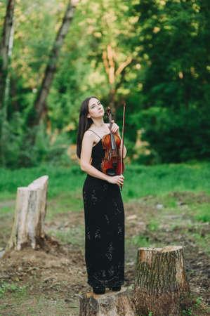 Mooi meisje in een zwarte jurk speelt viool in het bos