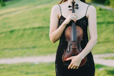 Violin in the hands of a beautiful woman in a black dress