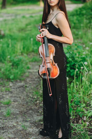 A young woman playing the violin in a magical forest