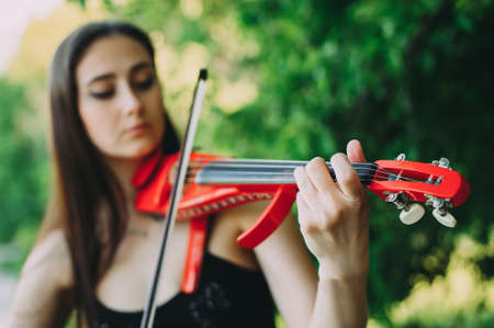 Beautiful girl with long hair holds a red electronic violin in her hand Zdjęcie Seryjne