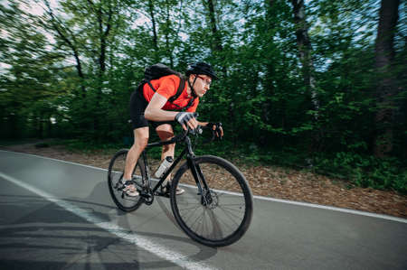 a professional cyclist in a helmet rides fast along a forest road