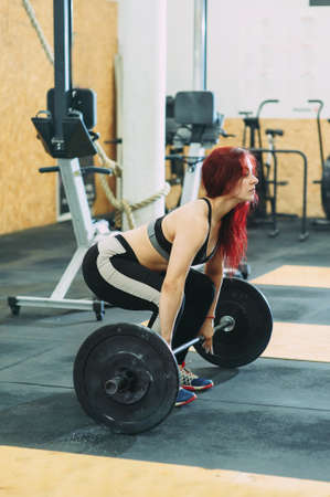 Woman at the gym using fitness equipment. athletic girl in top lifts a barbell