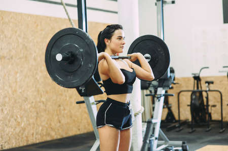 young strong girl is engaged with a barbell in the gym