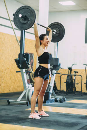 young strong girl is engaged with a barbell in the gym Stockfoto - 130101329