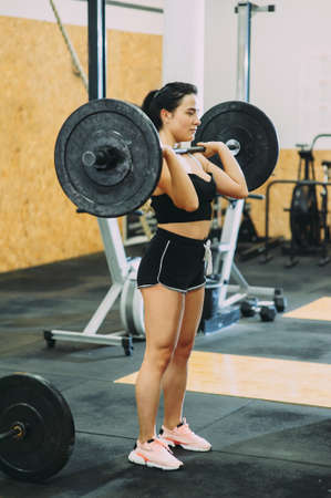 young strong girl is engaged with a barbell in the gym Stockfoto - 130101338